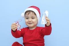 Маленький ребенок одетый как Санта Клаус с орнаментами в его руках стоковое фото rf
