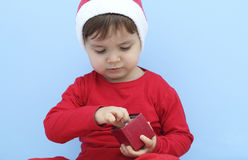 Маленький ребенок одетый как Санта Клаус с подарком стоковая фотография