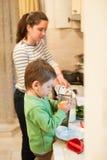 Маленький ребенок помогает его матери сварить стоковое изображение rf