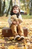 Маленький ребенок при медведь игрушки сидя на чемодане в осени стоковые фото