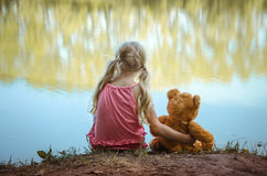 Маленький ребенок при плюшевый медвежонок сидя совместно задний взгляд Стоковое Фото