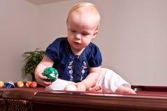 Маленький ребенок сидя на таблице биллиарда падая шарик в карманн Стоковое фото RF