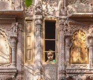 Маленький ребенок смотрит из деревянного Стоковое Изображение