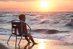 Маленький ребенок смотря заход солнца сидя морем стоковое изображение rf