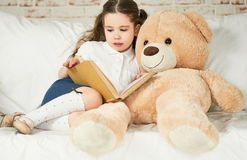 Маленький ребенок читая к ее другу плюша Стоковое Изображение