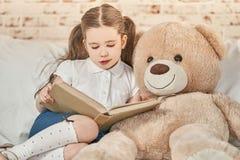 Маленький ребенок читая к ее другу плюша Стоковые Изображения