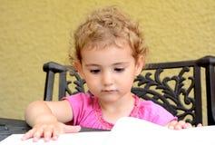 Маленький ребенок outdoors читая. Стоковая Фотография RF