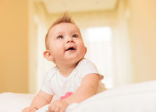 Маленький ребёнок сидя в ее кровати мечтает прочь Стоковое Изображение RF