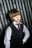 Маленький серьезный мальчик представляя в официальном костюме стоковое фото rf
