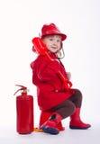 Маленький серьезный пожарный на белой предпосылке Стоковое Фото