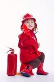 Маленький серьезный пожарный на белой предпосылке Стоковое фото RF