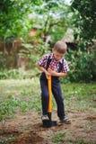 Маленький смешной мальчик с лопаткоулавливателем в саде Стоковые Фотографии RF