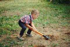Маленький смешной мальчик с лопаткоулавливателем в саде Стоковая Фотография RF