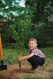 Маленький смешной мальчик с лопаткоулавливателем в саде Стоковое фото RF