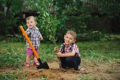 Маленький смешной мальчик с лопаткоулавливателем в саде Стоковые Изображения