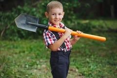 Маленький смешной мальчик с лопаткоулавливателем в саде Стоковое Фото