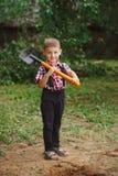 Маленький смешной мальчик с лопаткоулавливателем в саде Стоковые Фото