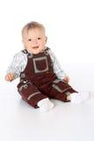 Маленький смешной младенец в прозодеждах сидя на поле внутри во всю длину Стоковые Фотографии RF