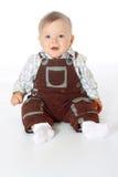 Маленький смешной младенец в прозодеждах сидя на поле внутри во всю длину Стоковая Фотография