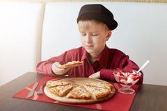 Маленький стильный ребенок в красной рубашке и черной крышке сидя в удобном кафе есть вкусные пиццу и мороженое принимать пролома Стоковые Фото