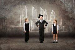 Маленький студент в академичной крышке с друзьями против чертежа города стоковое изображение rf