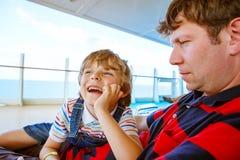 Маленький счастливый мальчик ребенк и его отец смеясь над и усмехаясь совместно стоковое фото rf