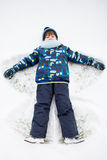 Маленький сладостный ребенок, мальчик, лежащ на снеге северного полюса, делая снег a Стоковые Изображения RF