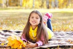 Маленький усмехаясь ребенок девушки лежа на шотландке с желтыми листьями клена в осени Стоковые Фото