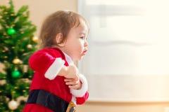 Маленький ход девушки малыша для того чтобы раскрыть подарки на рождество Стоковое фото RF