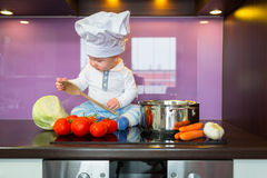 Маленький шеф-повар варя в кухне Стоковая Фотография