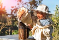 Маленький beekeeper дует курильщик для пчел Стоковые Изображения