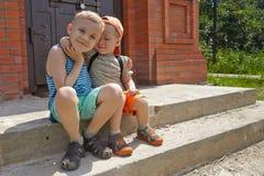 Маленький brotherssitting 2 в парке лета Стоковая Фотография RF