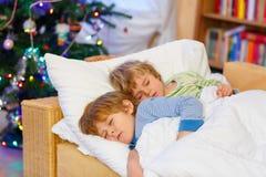 2 маленьких белокурых мальчика отпрыска спать в кровати на рождестве Стоковые Изображения