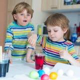 2 маленьких белокурых мальчика ребенк крася яичка на праздник пасхи Стоковая Фотография RF