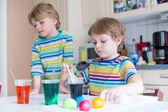 2 маленьких белокурых мальчика ребенк крася яичка на праздник пасхи Стоковые Изображения