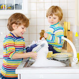 2 маленьких белокурых мальчика ребенк моя блюда в отечественной кухне Стоковое Изображение