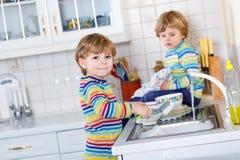 2 маленьких белокурых мальчика ребенк моя блюда в отечественной кухне Стоковые Фото