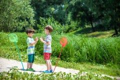 2 маленьких брать играя с бумажными шлюпками рекой на теплый и солнечный летний день Стоковое Изображение