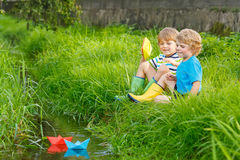 2 маленьких брать играя с бумажными шлюпками рекой Стоковое Фото