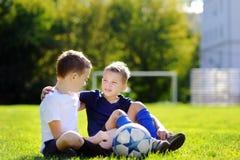 2 маленьких брать имея потеху играя игру футбола Стоковое фото RF