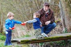 2 маленьких брать и их папа играя с бумажными шлюпками a Стоковое Изображение RF