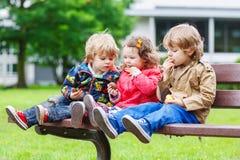 2 маленьких брать и сестра имея потеху в парке Стоковые Изображения