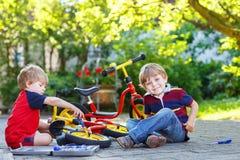 2 маленьких брать ремонтируя сломанный велосипед Стоковое Изображение RF
