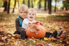 2 маленьких брать сидя на траве и обнимая с огромной тыквой в дне осени Стоковое Фото