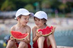 2 маленьких дет, братья мальчика, есть арбуз на beac Стоковая Фотография RF