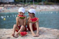 2 маленьких дет, братья мальчика, есть арбуз на beac Стоковое Изображение