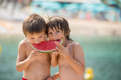 2 маленьких дет, братья мальчика, есть арбуз на beac Стоковое фото RF