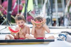 2 маленьких дет, братья мальчика, есть арбуз на beac Стоковая Фотография