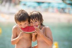 2 маленьких дет, братья мальчика, есть арбуз на beac Стоковое Фото