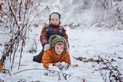 2 маленьких дет, братья мальчика играя и лежа в снеге outdoors во время снежностей Активный отдых с детьми в зиме на co Стоковое Изображение RF